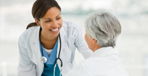 Young smiling doctor consoling older patient