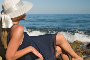 Lady in a dark blue dress and a hat romantically looks at the sea
