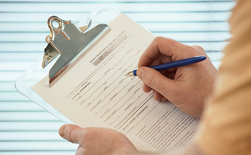 Stock image of a patient using a clipboard to fill out a patient form